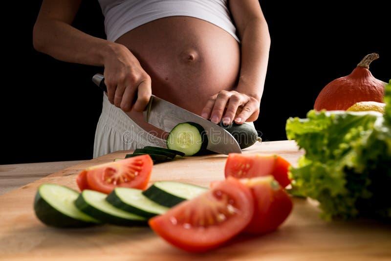 Kobieta w ciąży przygotowywa weganinu posiłek obraz royalty free