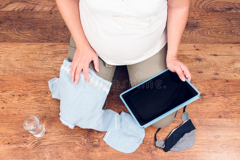 Kobieta w ciąży robi online zakupy na pastylce dla oczekiwać półdupków fotografia stock