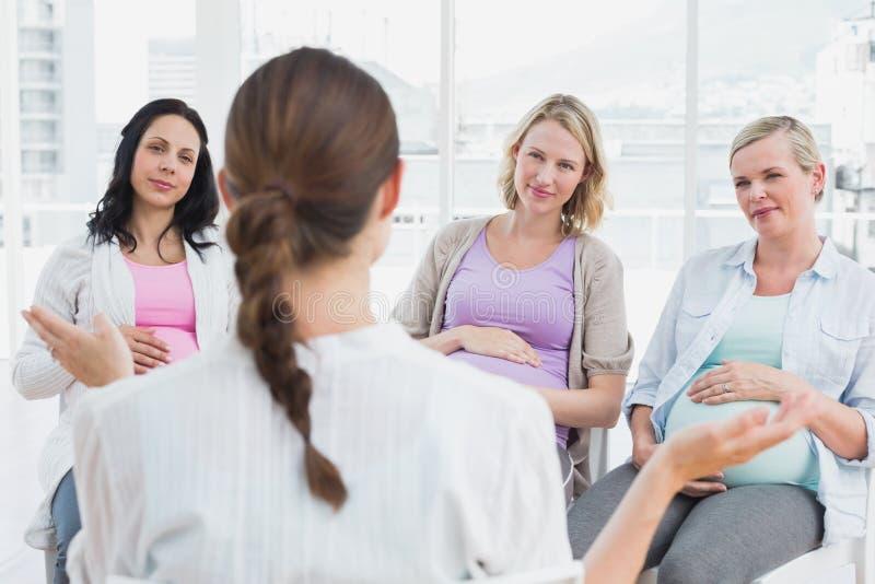 Kobieta w ciąży słucha gestykulować lekarkę przy przedporodową klasą fotografia stock