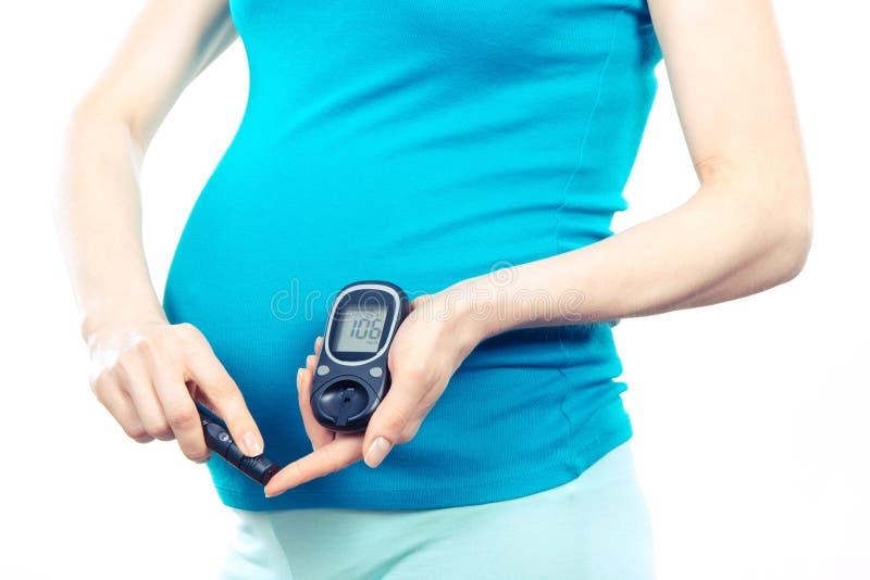 Kobieta w ciąży sprawdza cukier równego z glucometer, cukrzyce podczas brzemienności zdjęcie royalty free