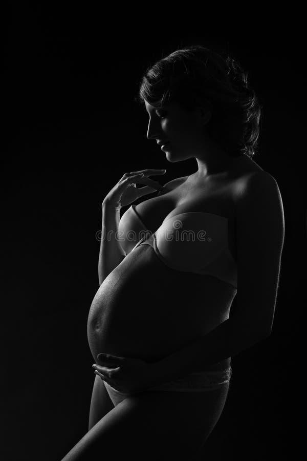 Kobieta w ciąży sylwetka nad czarnym tłem. Boczny widok. Sztuka obraz royalty free