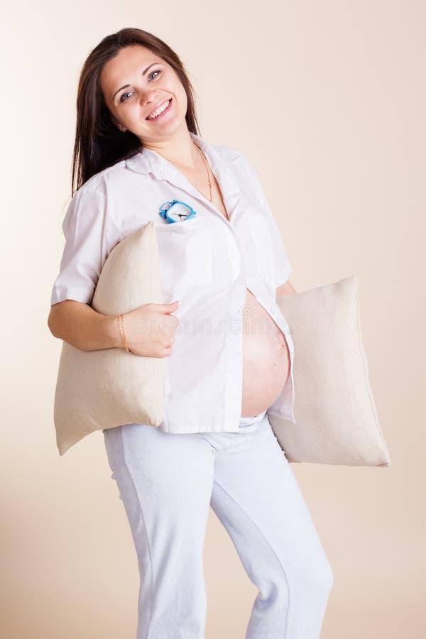 Kobieta w ciąży trzyma z poduszkami zdjęcie stock