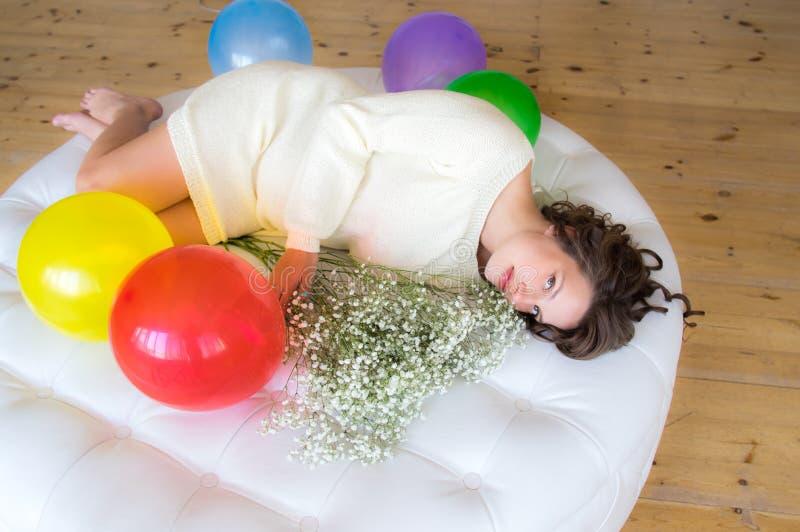 Kobieta w ciąży w biel sukni kłama na round kanapie fotografia royalty free