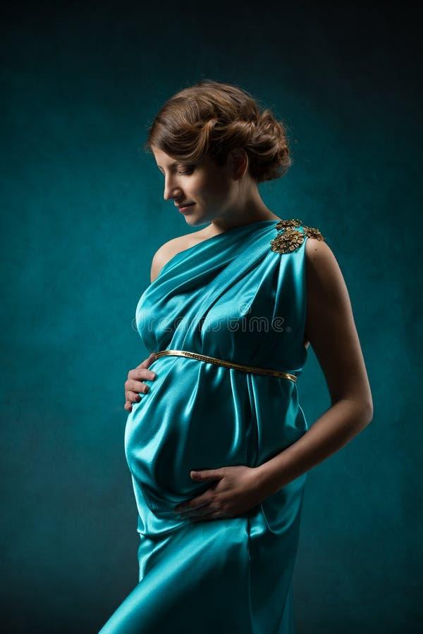 Kobieta w ciąży w długiej jedwab sukni nad błękitnym sztuki tłem. zdjęcie royalty free