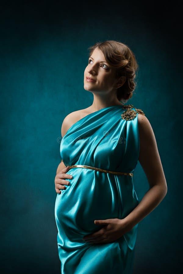 Kobieta w ciąży w długiej jedwab sukni nad błękitnym sztuki tłem. obraz stock