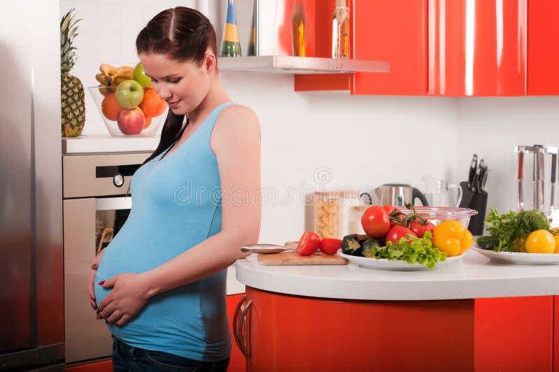 Kobieta w ciąży w kuchni zdjęcia stock