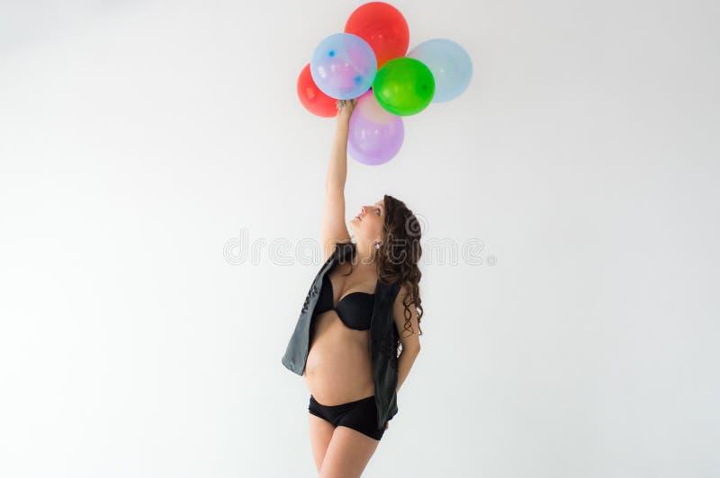 Kobieta w ciąży z balonami i rękami nad głowa zdjęcie royalty free