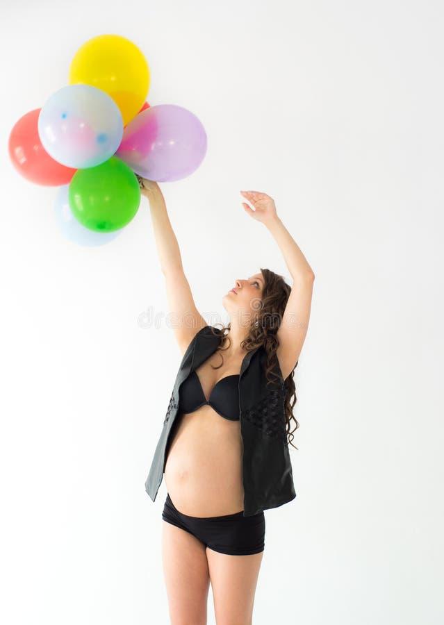 Kobieta w ciąży z balonami i rękami nad głowa zdjęcie stock