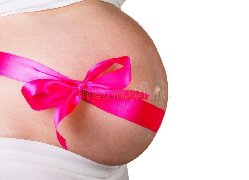 Kobieta w ciąży z czerwonym łękiem na jej żołądku w antycypaci dziewczynie odizolowywał białego tło obraz royalty free