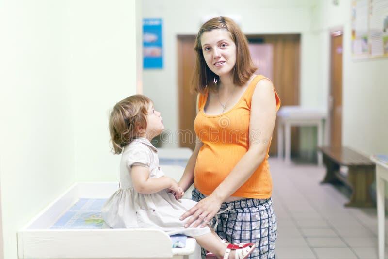 Kobieta w ciąży z dzieckiem przy kliniką fotografia stock
