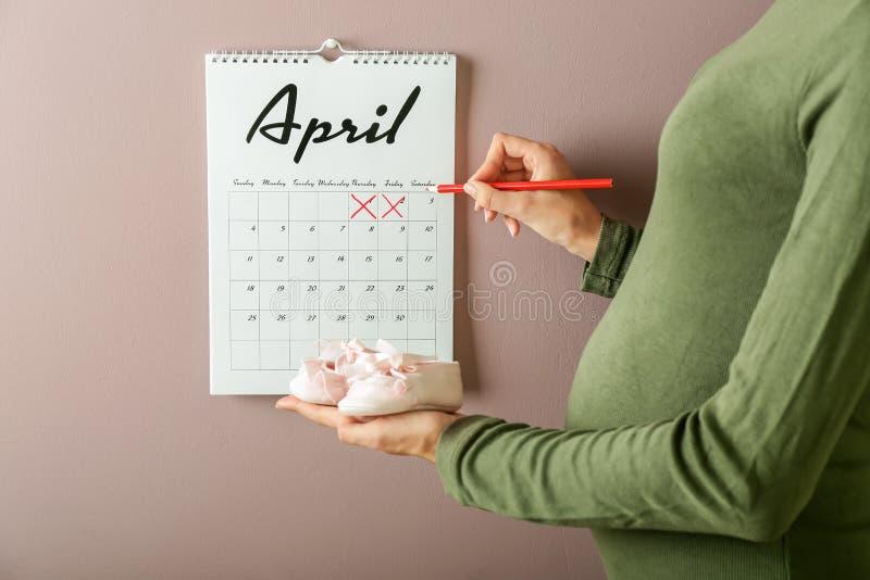 Kobieta w ciąży z dziecko butów pobliskim kalendarzowym obwieszeniem na ścianie obraz stock