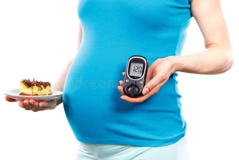 Kobieta w ciąży z glucometer i kawałkiem cheesecake, cukrzyce i cukier równi podczas brzemienności, zdjęcia stock