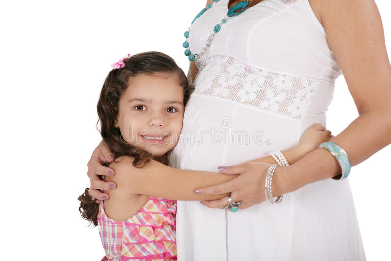 Kobieta w ciąży z jej córką. Odizolowywający na białych półdupkach obraz stock