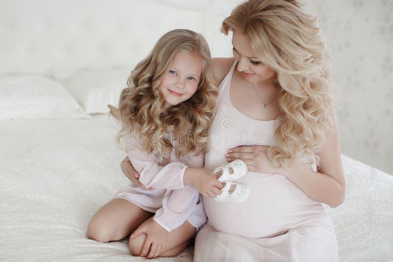 Kobieta w ciąży z małą córką w jaskrawej sypialni zdjęcia stock