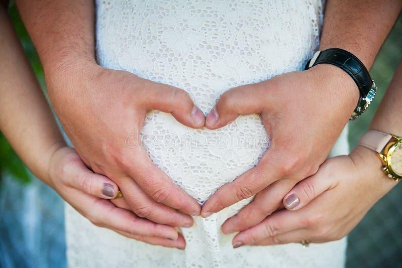 Kobieta w ciąży zawijają jej ręki wokoło brzucha fotografia royalty free