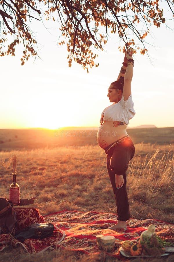 Kobieta w ci??y robi joga w polu przy zmierzchem Dziewczyna trzyma wymarzonego łapacza i robi ćwiczeniu obraz stock