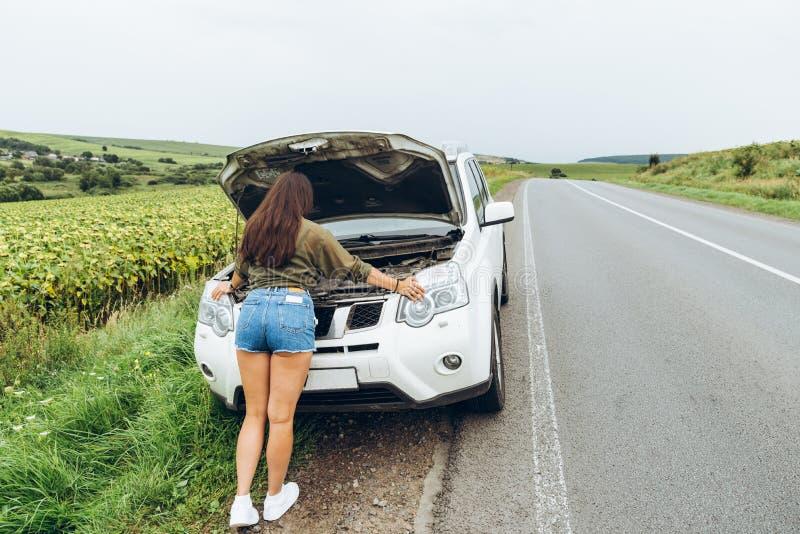 Kobieta w ciasnych koszula nowym łamającym samochodzie z rozpieczętowanym kapiszonem obraz royalty free