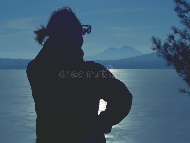Kobieta w ciepłych ubraniach cieszy się sunbathing przy zamarzniętym jeziorem fotografia royalty free