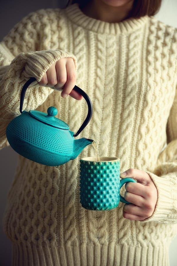 Kobieta w ciepłym trykotowym woolen pulowerze trzyma turkusowego teapot i nalewać ziołowej herbaty w handmade filiżankę kosmos ko zdjęcie royalty free