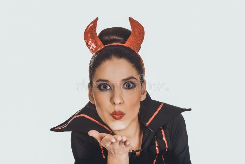 Kobieta w czarcim kostiumowym dmuchaniu buziak fotografia stock