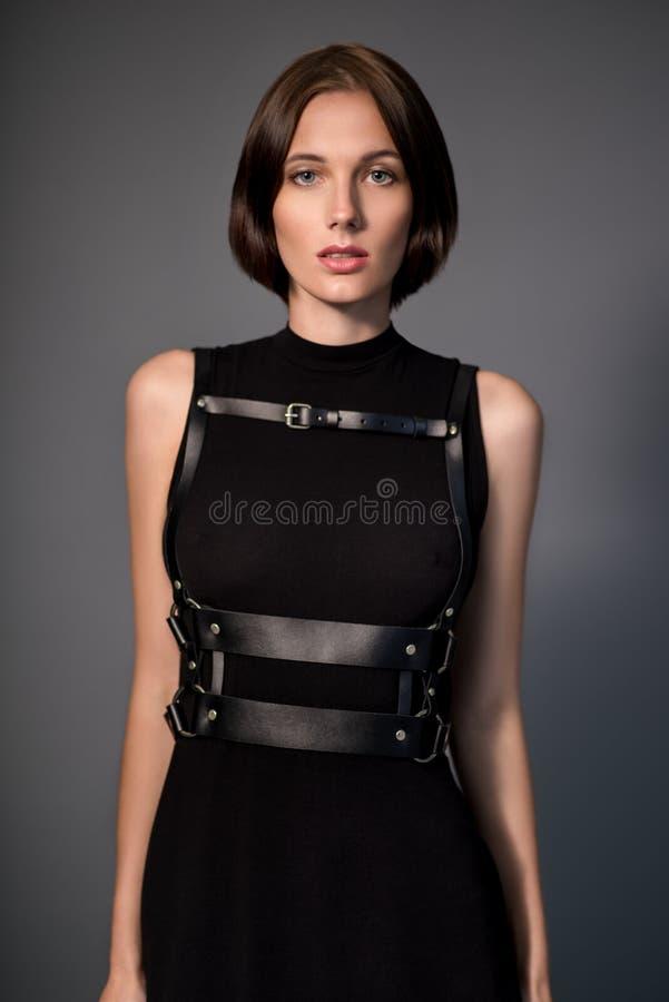Kobieta w czerni sukni z rzemiennymi akcesoriami zdjęcie royalty free