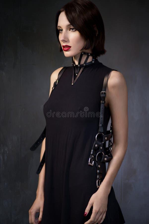 Kobieta w czerni sukni z rzemiennymi akcesoriami obrazy royalty free
