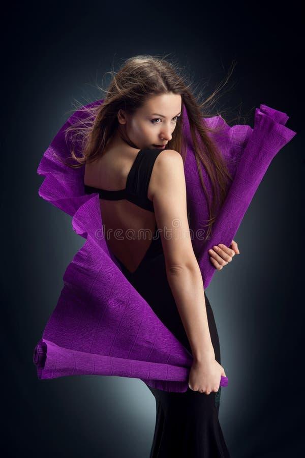 Kobieta w czerni sukni zawijającej w purpura gofrującym papierze pozuje patrzeć daleko od fotografia royalty free