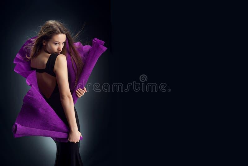 Kobieta w czerni sukni zawijającej w purpura gofrującym papierze pozuje patrzeć daleko od zdjęcie royalty free