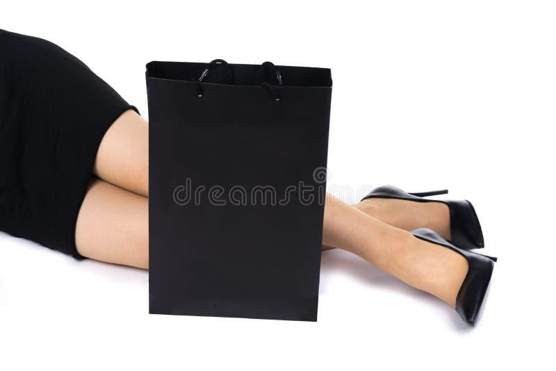 kobieta w czerni szpilkach z torba na zakupy w przodzie na białym tle i sukni obraz stock