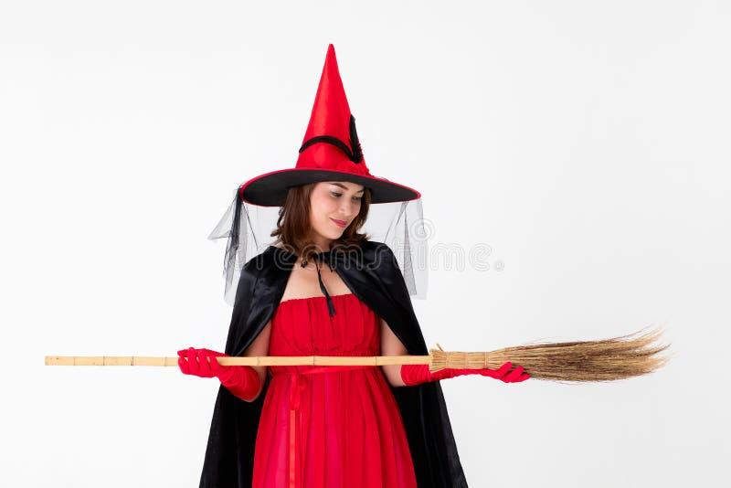 Kobieta w czerwieni sukni kostiumu dla famale czarownicy mienia broomstick o zdjęcia royalty free