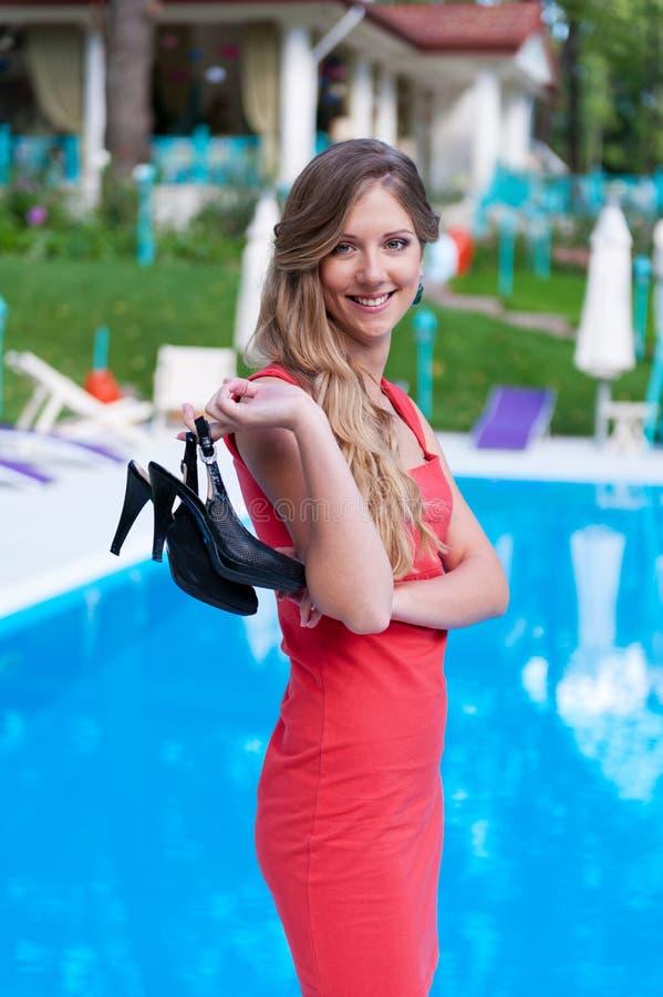 Kobieta w czerwieni sukni mieniu jej sandały zdjęcie stock