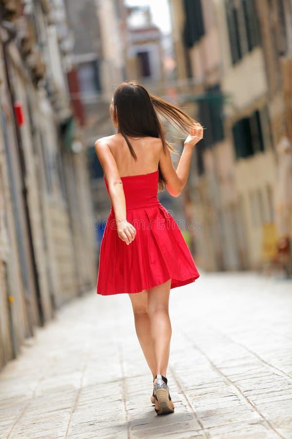 Kobieta w czerwieni sukni odprowadzeniu w ulicie w Wenecja obraz stock