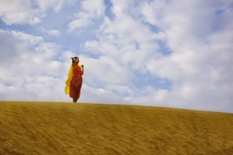 Kobieta w czerwieni sukni pozycji w pustyni fotografia royalty free