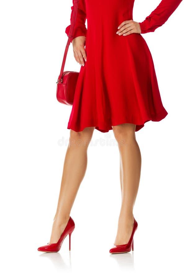 Kobieta w czerwieni sukni pozycji z czerwoną kiesy torbą, butami i fotografia stock