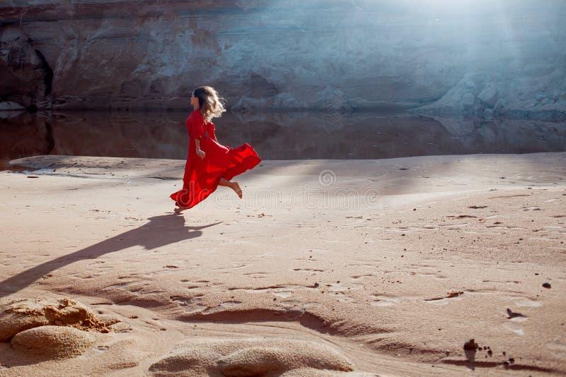 Kobieta w czerwonej falowanie sukni z latającą tkaniną biega fotografia stock