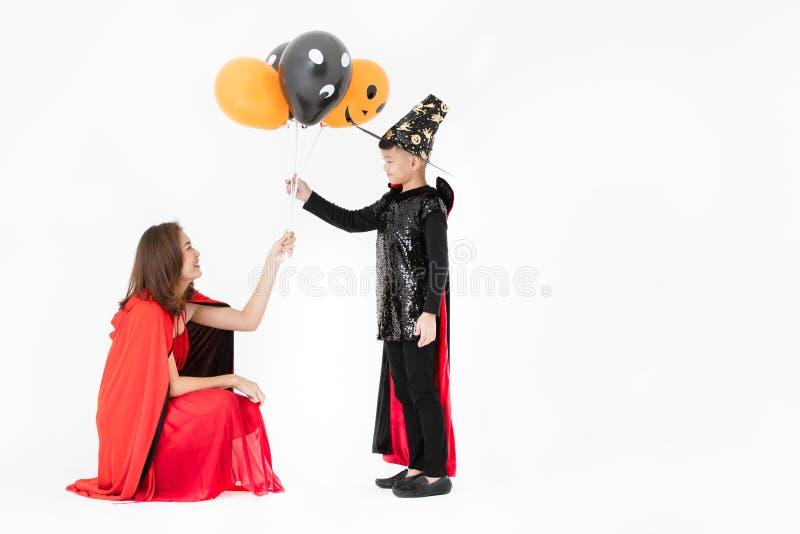 Kobieta w czerwonej kostiumowej daje fantazji szybko się zwiększać żartować chłopiec w tylnym su zdjęcie stock