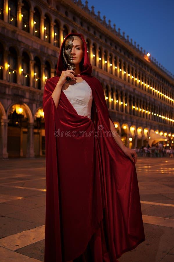 Kobieta w czerwonej pelerynie w Wenecja fotografia stock