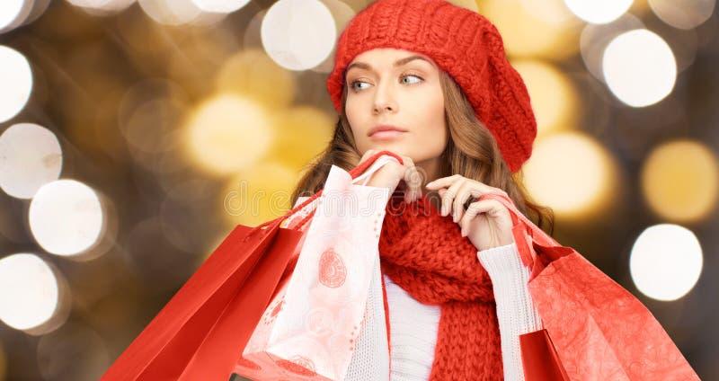Kobieta w czerwonych kapeluszu i szalika mienia torba na zakupy obraz stock