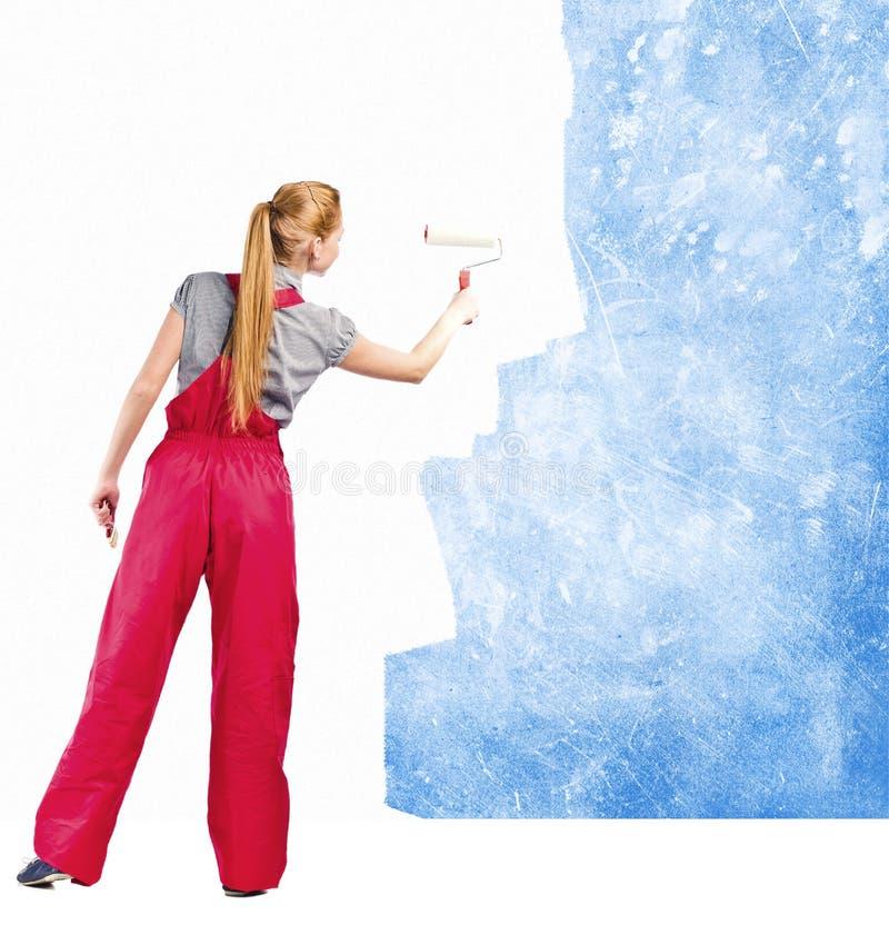 Kobieta w czerwonych kombinezonach maluje brudnawą ścianę obraz stock