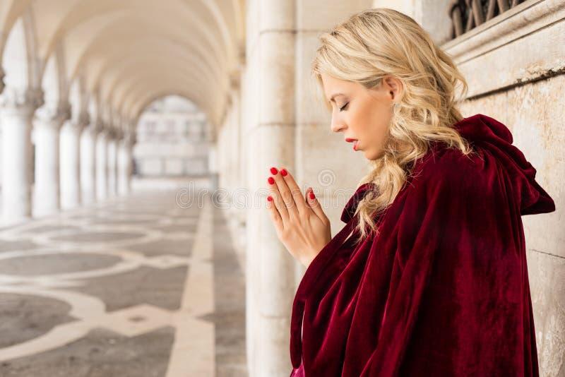 Kobieta w czerwonym peleryny modleniu obrazy royalty free