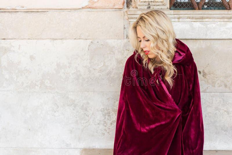 Kobieta w czerwonym peleryny obsiadaniu na ławce zdjęcia royalty free