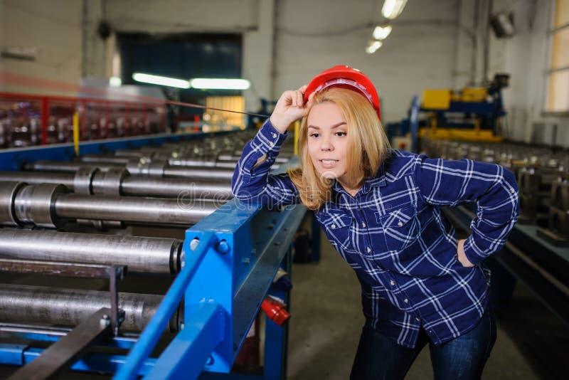 Kobieta w czerwonym zbawczym hełmie przy metalu dachówkowego dachu rękodzielniczym fact fotografia royalty free