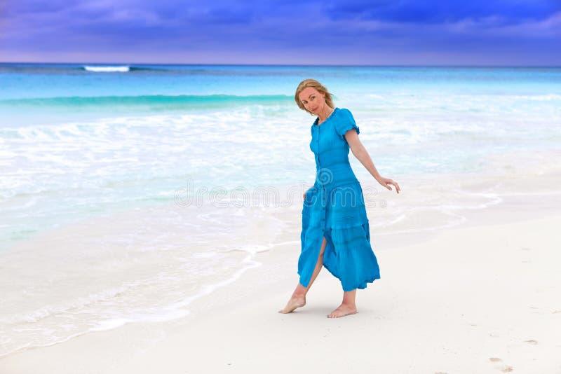 Kobieta w długiej błękit sukni na burzowym dennym wybrzeżu fotografia royalty free