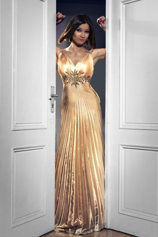Kobieta w długiej złotej partyjnej sukni obraz royalty free