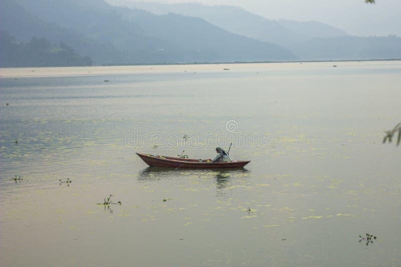 Kobieta w drewnianej łodzi na jeziorze łowi z siecią przeciw tłu góry obrazy stock