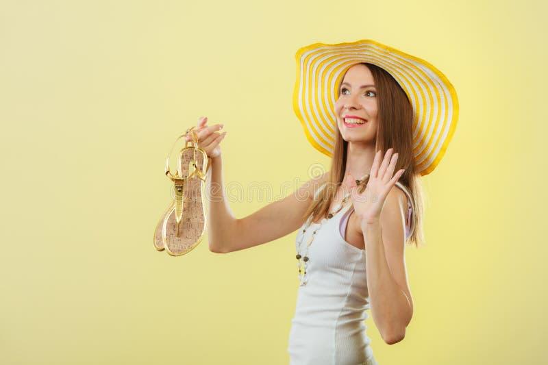 Kobieta w dużym żółtym lato kapeluszu trzyma sandały obraz stock