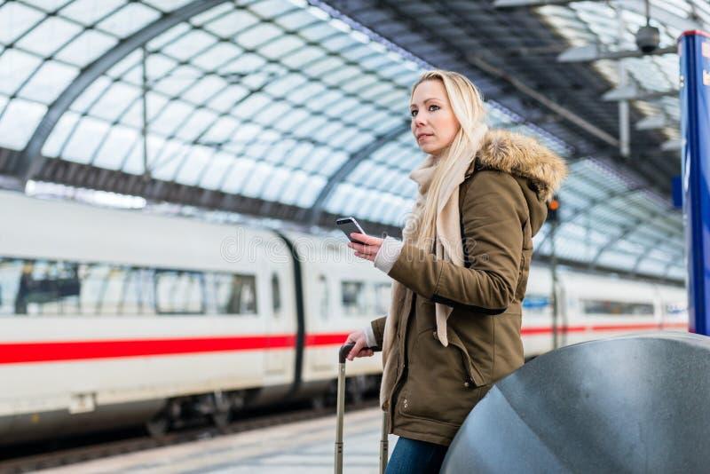 Kobieta w dworcu używać rozkład zajęć app na telefonie obraz stock