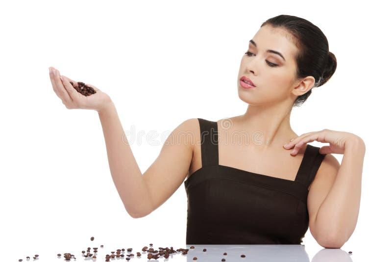 Kobieta w elegancki uzupełniam bawić się z kawowymi fasolami obrazy stock