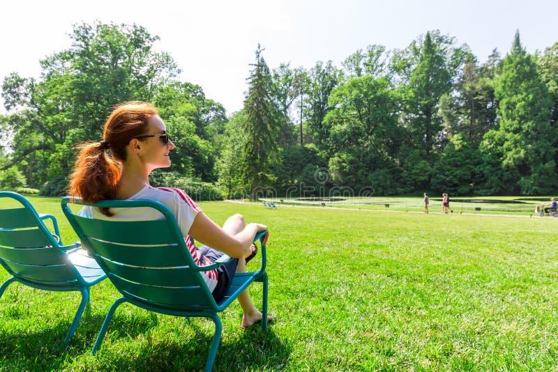 Kobieta w eyeglasses relaksuje na greenfield zdjęcie stock