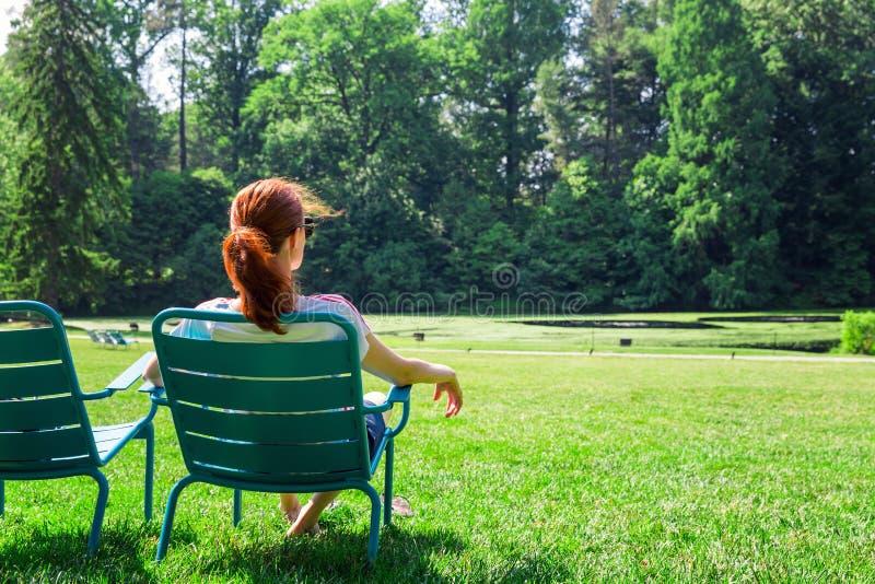 Kobieta w eyeglasses relaksuje na greenfield zdjęcia royalty free